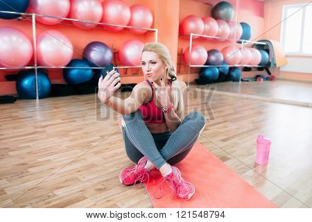 Athletic girl makes fitness selfie in gym