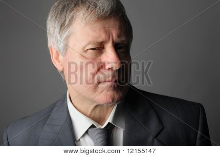 portrait of senior businessman with suspicious expression