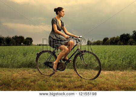 pretty woman riding bicycle in the countryside