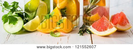 Selection of infused water in glass bottles, rustic wood background