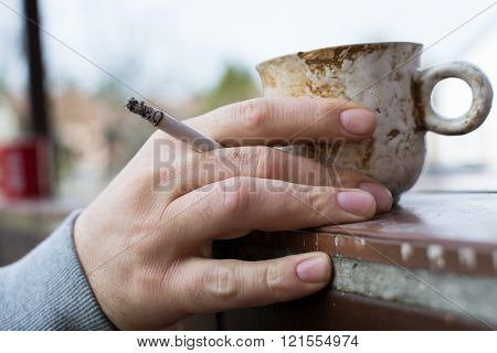 Man holding a cigarette in hand with cup of coffee outdoor. No smoking. Quit smoking.