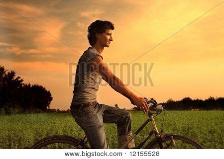 bicicleta de montar a caballo joven en el campo