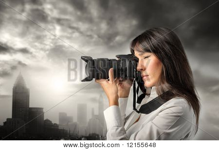 Woman taking picture of modern city  with camera