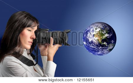 Woman taking picture of planet earth with camera
