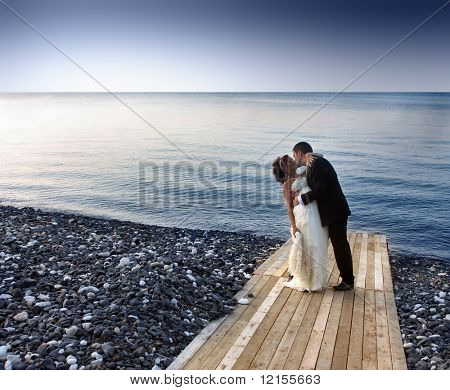 bride and groom kissing on a wharf
