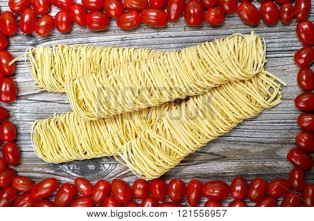 Homemade fettuccini pasta and small red tomatoes on wooden background diet and food concept. Closeup.