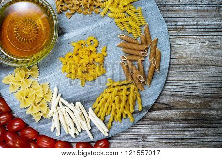 Various Mix Of Pasta, Small Red Tomatoes And Olive Oil On Wooden Plate