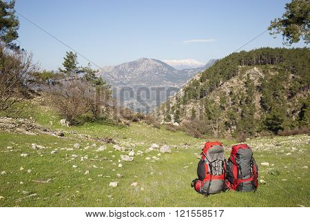 Camping with backpacks in the mountains on a sunny summer day.