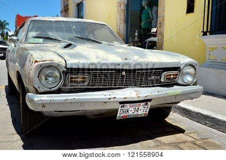 Campeche Mexico - February 18 2014: A street in Campeche with damage old Maverick car