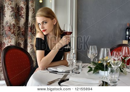 beautiful woman drinking red wine in a luxury restaurant