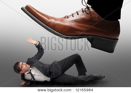 big male shoe stepping on a little businessman