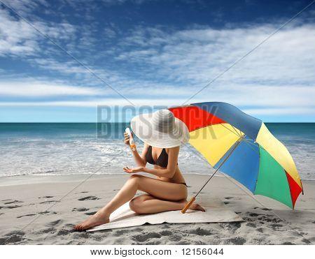 woman in bikini applying protective lotion on the beach