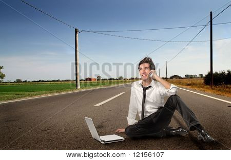 young businessman talking at mobile phone and using laptop on the street