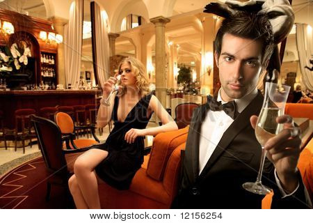 elegant young couple drinking wine in a luxury interior