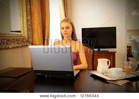 woman with laptop and breakfast in a hotel room