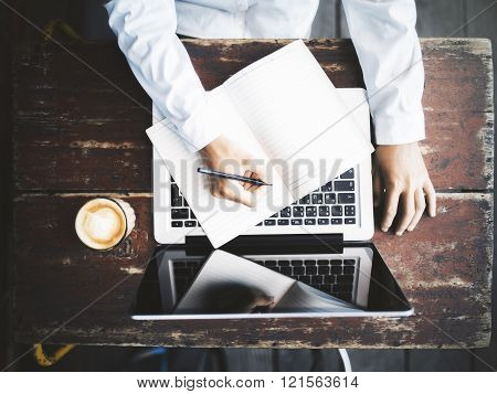 Man Writing In Notepad With Laptop And Coffee Mug On Wooden Table