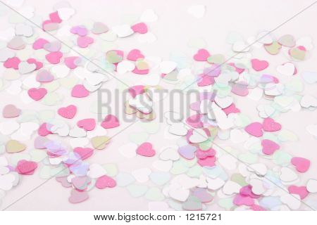 heart shaped confetti tossed on white