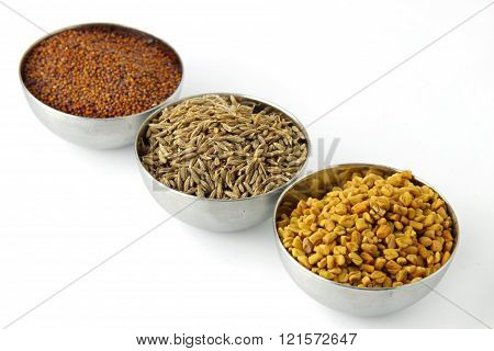 Three steel bowls with cumin fenugreek seeds, cumin seeds and mustard seeds isolated on white.