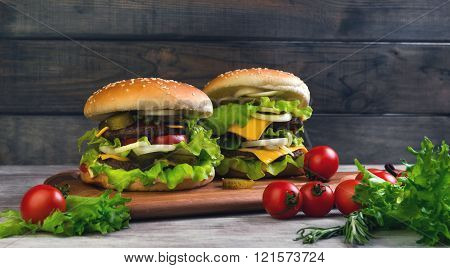 Two big cheeseburger deluxe high on light wooden background in rustic style