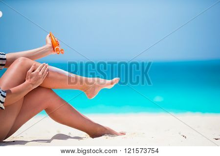 Young woman apply cream on her body at beach
