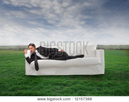 businessman sleeping on the sofa in a grass field