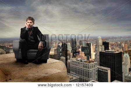 businessman seated in a armchair on  the top of new york city building