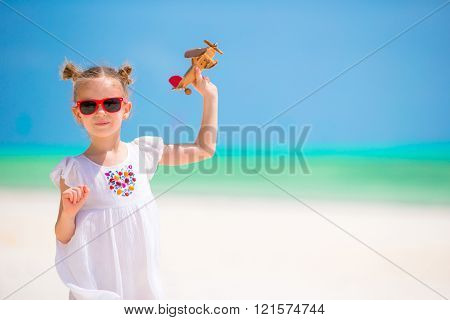 Adorable little girl with toy airplane on white beach
