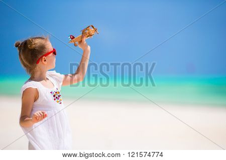Happy little girl with toy airplane during beach vacation