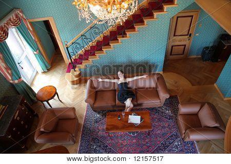 vista superior da bela mulher sentada no sofá da sala de estar de luxo