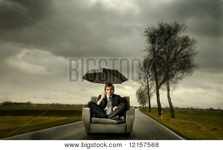 businessman with umbrella in a stormy landscape