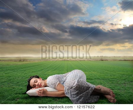 woman in nightgown sleeping in a grass field