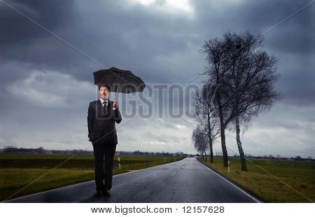businessman with umbrella on the road