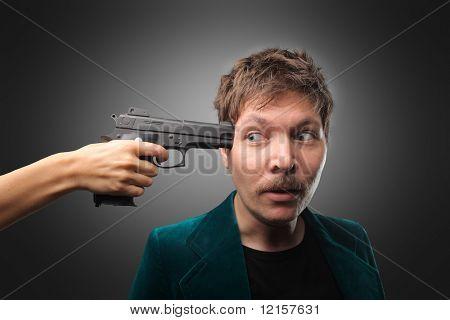señalar la pistola contra la cabeza del hombre de la mano