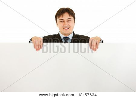 Smiling modern businessman holding blank billboard isolated on white