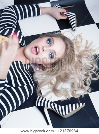 Surprised young attractive blonde woman lying down on a checkered floor with high heel stiletto shoes, fashion concept