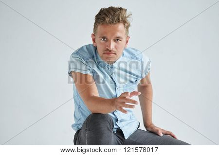 Brutal man in a shirt with short sleeves sitting in the chair his fists clenched slightly bent liste