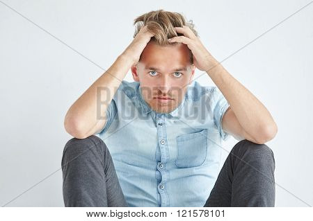 Brutal man in a shirt with short sleeves sitting on the floor under the gaze of the forehead holding