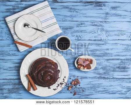 Round Twisted Bun Danish snail poured chocolate icing white cup of coffee espresso cinnamon sticks pieces of chocolate with hazelnuts on a blue wooden top view empty place for text