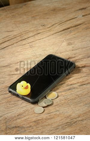 Smart phone with yellow rubber duck on background of wooden.