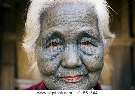SAW, MYANMAR - DECEMBER 10, 2015: Photo of a tattooed faced Chin woman ((Uppriu tribe - totally black face). Chin people, also known as the Kukis are a number of Tibeto-Burman tribal people.