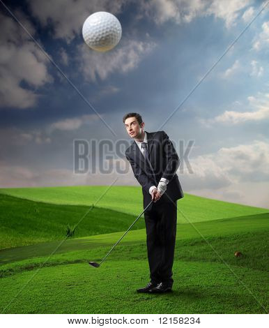 businessman shots a golf ball in a grass field