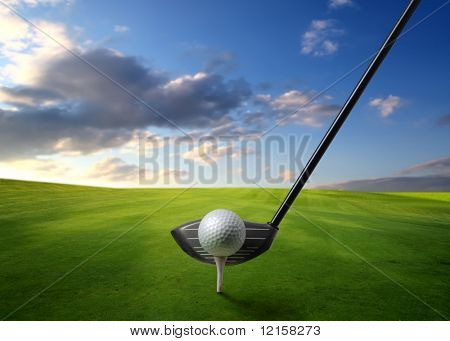 Detail of golf club and ball on a green meadow