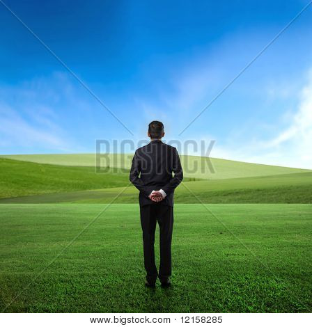 Man standing in the middle of a green meadow and observing the panorama in front of him