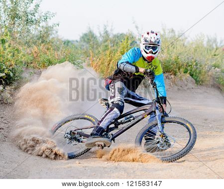 ZAPORIZHZHYA, UKRAINE - AUGUST 04, 2015: Fully Equipped Professional Downhill Cyclist Riding the Bike on the Dusty Trail. Extreme Sports