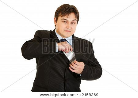 Successful young businessman putting money in pocket isolated on white