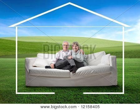 Senior pareja sentada en un sofá y rodeado por la forma de una casa