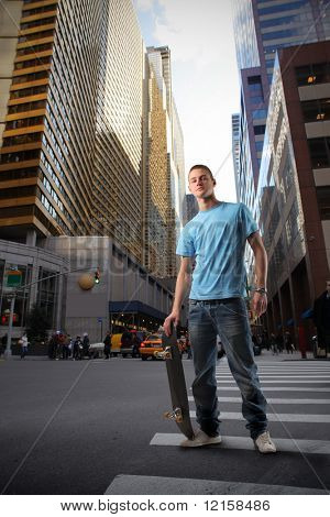 Portrait of a young man in trendy clothes holding a skateboard in the middle of a city street