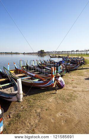 AMARAPURA, MYANMAR - NOVEMBER 27, 2015: Photo of a Burmese man painting small wooden boats near U Bein Bridge.