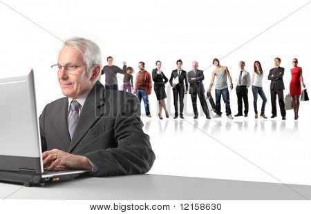 Portrait of a senior businessman working on a laptop with some people on the background