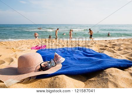Hat, towel, sunglasses and slippers on a tropical beach. Concept of summer vacations.